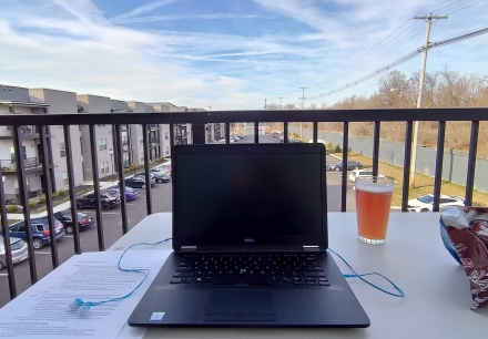 Balcony with a laptop on a table, with food.